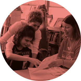 An image of two women, smiling and enthusiastically helping a young girl complete a worksheet. They are in a library or setting that has a lot of books behind them. One of the women is sitting next to her and the other is behind her with her arm around the girl