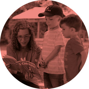 A woman with curly hair and glasses smiling as she kneels next to two young boys, one wearing a baseball cap and reads a book to them.