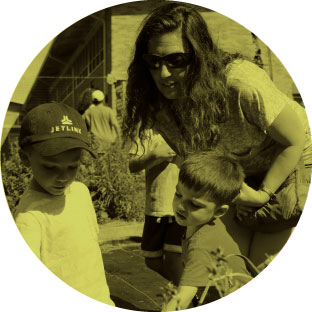 A woman with sunglasses bends over to talk to two young children who are playing, one of them wearing a baseball cap.