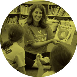 A woman wearing a jkidphilly shirt, smiling as she enthusiastically reads a book to young children sitting in front of her.